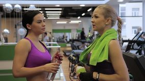 The two young beautiful women is standing in the modern gym and drinking water. The blond female athlete has green towel on her shoulders and her brunette stock video footage