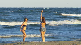 Two young beautiful women in swimsuit taking pictures with smart phone and having fun at the beach stock footage