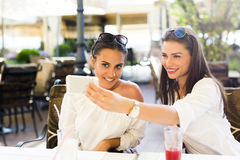 Two young beautiful women taking a selfie of themselves Stock Photography