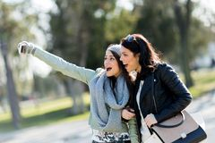 Two young and beautiful women taking a selfie of themselves on a Stock Photos