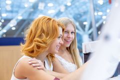 Two young beautiful women in a travel agency choosing a vacation trip, using the interactive screen. Two young beautiful women in a travel agency choosing a stock photography