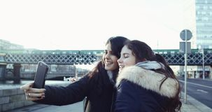 Two young and beautifull girl with long hair making selfie on the smartphone sitting in front of train bridge. Shot in stock video footage