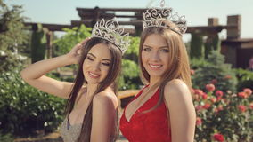 Two young beauty contest winner in long evening. Two young beauty contest winner in the long evening dresses and crowns in the garden with roses stock video