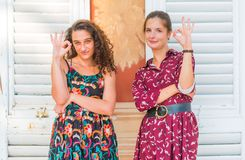 OK hand sing, We approve. Two young best friend giving the OK hand sign and approving royalty free stock image