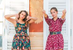 Two thumbs down by young girls. Two young best friend giving two thumbs down and disapproving royalty free stock image