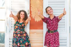 Two thumbs up by young girls. Two young best friend giving two thumbs up and approving stock photography