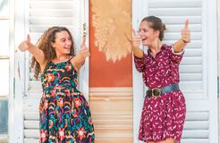 Two thumbs up by young girls. Two young best friend giving two thumbs up and approving stock images
