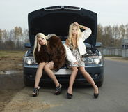 Two young blond beautiful women with broken car Royalty Free Stock Photography