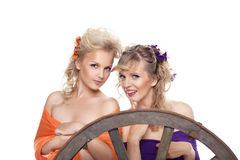 Two young blond woman with flowers in hairs smile Stock Photography