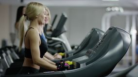 Two young blond women walking on treadmill. Talking and smiling to each other stock video