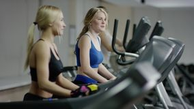 Two young blond women walking on treadmill. Talking and smiling to each other stock footage