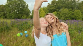 Two young blonde girls are photographed on the phone. Make selfie. Two beautiful young girls taking self portrait outdoors on green spring park background stock video