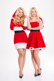 Two young blonde sisters twins in santa claus costumes Royalty Free Stock Images