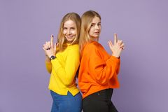 Two young blonde twins sisters girls in colorful clothes standing back to back, keeping fingers like gun  on stock photos