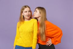 Two young blonde twins sisters girls in colorful clothes whispering gossip and tell secret with hand gesture isolated on stock photography