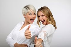 Two blond women smiling thumbs up. Two young blonde women having fun Stock Photo