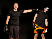 Two young boxers fooling around together. With the one standing facing the camera with a grin while punching sideways at his friend who is ducking out of the Royalty Free Stock Image