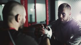 Young boxers preparing for sparring. Two young boxers preparing for sparring, shaking hands in kickboxing gloves stock video