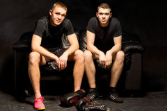 Two young boxers relax before a training session. Sitting together on a black sofa with their gloves on the floor in front of them looking st the camera with Royalty Free Stock Images
