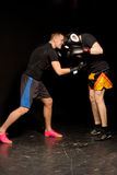Two young boxers sparring in the ring. During a training session as the one goes in for a low blow punch to his opponents abdomen Stock Photos