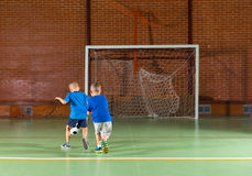 Two young boy friends playing soccer. Together on an indoor court as they relax during the summer vacation running away from the camera towards the goal Royalty Free Stock Image