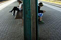 Young boy and girl sitting and waiting a train while using their cellphones. Two young, boy and girl, sitting at a train station platform waiting and playing Royalty Free Stock Photo