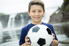 Two young boy outdoors with soccer ball smiling Stock Photos