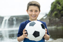Two young boy outdoors with soccer ball smiling Royalty Free Stock Photos