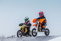 Two young boy racers on motorcycle ride through hill of motocross Stock Photo