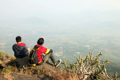 Two Young boys with backpack taking sitting on the top of a mountain and enjoying valley view Royalty Free Stock Images