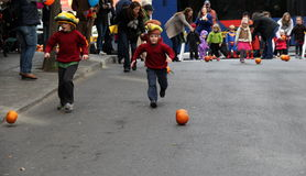 Two young boys chasing pumpkins down Caroline Street for the annual pumpkin roll,Saratoga Springs,New York 2013. Stock Photo