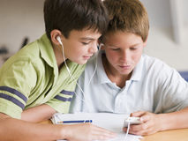 Two Young Boys Distracted From Their Homework Royalty Free Stock Photos