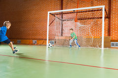 Two young boys enjoying a game of soccer. On an indoor court with one kicking the ball and the other playing goalkeeper Royalty Free Stock Photo