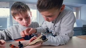 Two boys are finishing their wooden drone model. Two young boys are finishing their wooden drone with tools stock video footage