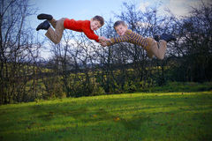 Two young boys flying outdoors Royalty Free Stock Photography