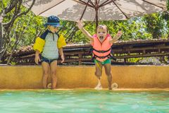 Two young boys friends jumping in the pool stock photo