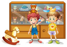 Two young boys in front of a cabinet with toys Royalty Free Stock Image