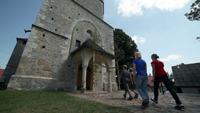 Two young boys, girls visiting old parish church. A church and group of young people visiting parish church stock footage