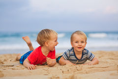 Two young boys having fun on a beach, happy friends laughing Stock Photos