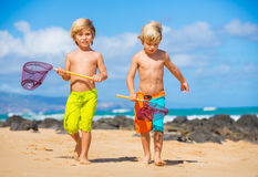 Two young boys having fun on tropcial beach Royalty Free Stock Image