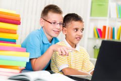 Two young boys at home looking at the laptop Royalty Free Stock Image