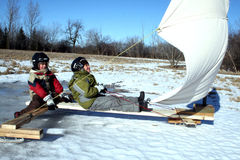 Two Young Boys On Ice Boat With Sails stock image