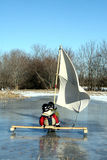 Two Young Boys On Ice Boat With Sails. Two young boys are sailing on the rink with their ice boat Royalty Free Stock Photo