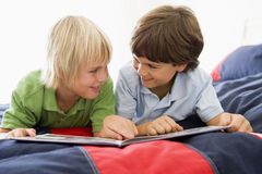 Two Young Boys Lying Down On A Bed Reading A Book Royalty Free Stock Photo