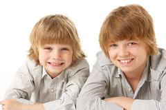 Two Young Boys Lying On Stomach In Studio Royalty Free Stock Photography