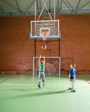 Two young boys playing basketball together Stock Photos