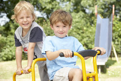 Two Young Boys Playing on Bike stock image