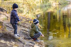 Two young boys playing fishing with sticks near pond in fall park. Little brothers having fun near lake or river in autumn. Happy