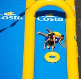 Two young boys playing in the longest water slide entered in the Guinness Book of Records showed for the Costa Cruises Festival in Stock Images