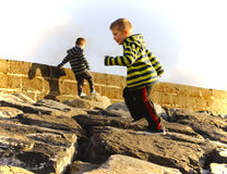 Two young boys playing outdoors. Two young boys playing on rocks near a wall outdoors on a sunny day Stock Images